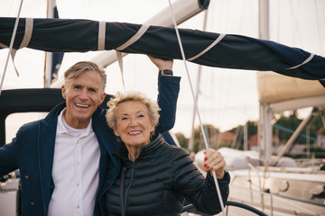 Portrait of smiling senior couple standing in yacht