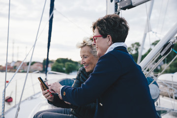 Smiling senior women using mobile phone on yacht