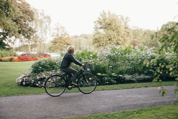 Full length of senior woman riding bicycle in park