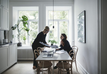 Female colleagues discussing over document at table in home office