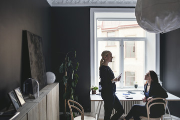 Female coworkers discussing by desk at home office