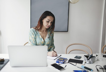 Businesswoman working at table in home office