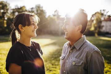 Close-up of smiling father and daughter talking while standing on grassy field at park during sunny day