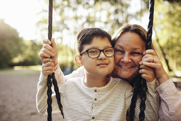Portrait of smiling mother with son playing on swing at playground