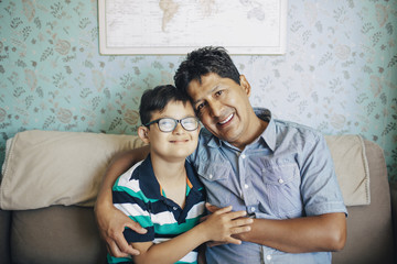 Portrait of smiling father and son sitting on sofa against wall at home