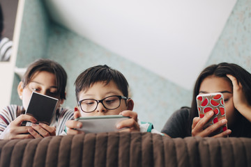 Low angle view of boy looking at digital tablet while lying with sisters using mobile phone on bed at home