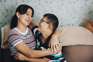 Loving brother and sister embracing on sofa against wall in living room