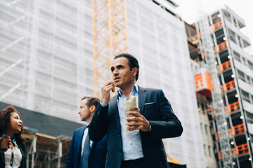 Low angle view of businessman eating wrap sandwich while standing by colleagues against building in city