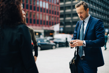 Mature businessman using mobile phone while standing by female colleagues in city