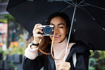 Smiling woman carrying umbrella photographing through camera in city