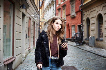 Young woman with mobile phone looking away while standing in alley