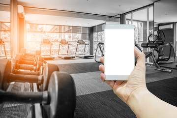 hand hold smartphone Rows of dumbbells in the gym with hign contrast and monochrome color tone