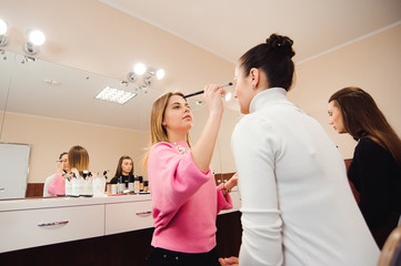 Professional make-up artists work with beautiful young women. School of professional make-up