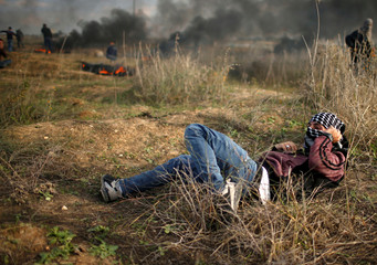 Palestinian demonstrator takes cover during clashes with Israeli troops at a protest near the border with Israel in the east of Gaza City