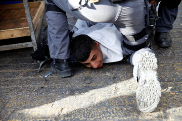 """Israeli policemen detain a Palestinian protestor after Friday prayers in Jerusalem's Old City, as Palestinians call for a """"day of rage"""" in response to President Donald Trump's recognition of Jerusalem as Israel's capital"""