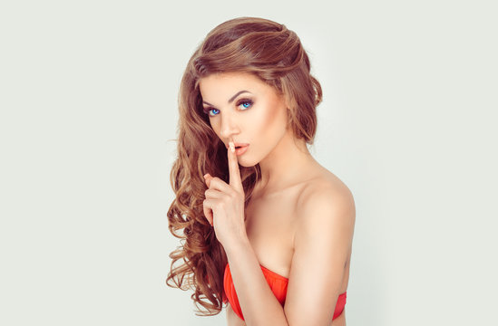 Hush. Woman wide eyed asking for silence or secrecy with finger on lips shh hand gesture white background wall. Pretty girl placing fingers on lips shhh sign symbol. Negative emotion facial expression