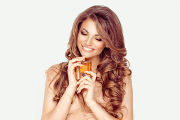I adore my perfume. The happy woman smiling holding has a perfume in hands, long curly brown hair isolated white background.