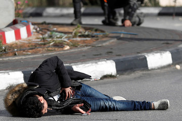 A Palestinian man with a knife and what looks like an explosive belt lies on the ground after being shot by Israeli border policemen near the Jewish settlement of Beit El, near the West Bank city of Ramallah