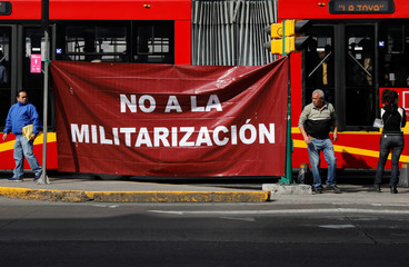Activists hold a protest against a law that militarises crime fighting in the country outside the Senate in Mexico City, Mexico