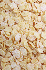 Corn flakes texture closeup pattern as background. Breakfast food photo. Cereals.