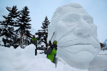 Sculptors carve a giant head snow sculpture representing late French singer Johnny Hallyday in Val d'Isere