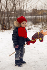 boy on a toy horse is standing on the street in winter at Christmas