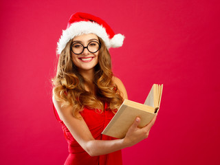 Young attractive Santa girl in red dress holding book over red background