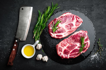 Cooking on kitchen table fresh raw pork marbled steaks on black background, top view