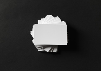 Photo of blank white business cards on black paper background. Template for ID. Flat lay.