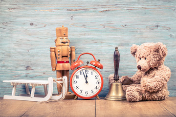Teddy Bear toy, bronze bell, retro clock, nutcracker and wooden sleigh front textured wall background. Christmas greeting card concept. Vintage instagram style filtered photo