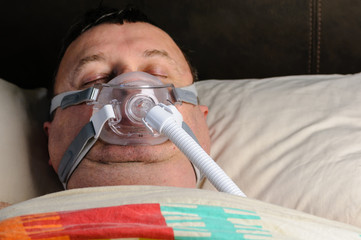 A middle-aged, overweight man wearing a CPAP mask while sleeping in bed