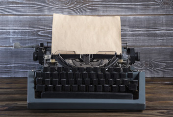 Vintage typewriter with old blank paper on a wooden table
