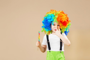 Happy clown boy in large colorful wig. Let's party! Funny kid clown. 1 April Fool's day concept. Portrait of a child eating lollipop.