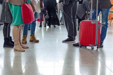 Group of people are standing with suitcases and bags standing in the airport hall. Copy space.