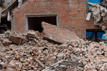 the ruins of collapsed houses, piles of brick construction waste