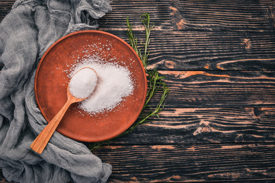 Salt in a wooden spoon on a plate. On a wooden background. Top view. Free space for text.