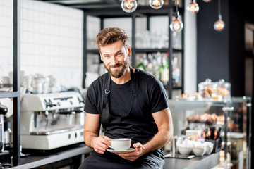 Fototapeta Portrait of a handsome barista sitting with coffee at the bar of the modern cafe interior obraz