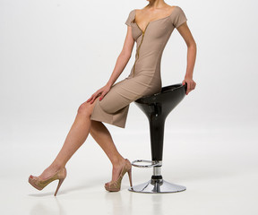 Model Seated in a Tan Form fitting Bodycon Dress