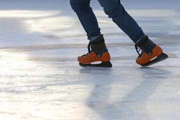 the legs of a man skating on the ice rink.