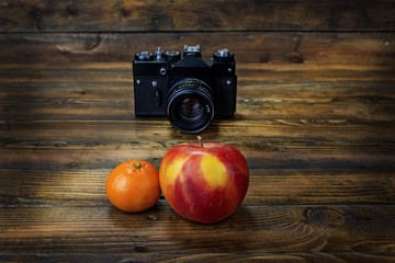 Film camera shoots mandarine and apple  on wooden background