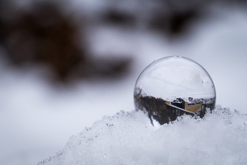 A crystal ball on a snow pile is reflecting surrounding