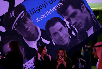 Saudi women stand in front of a poster of actor John Travolta at APEX Convention Center in Riyadh
