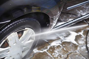 View of car wash closeup, washing modern car by high pressure water