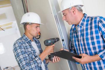 carpenter with student in workshop assembling door