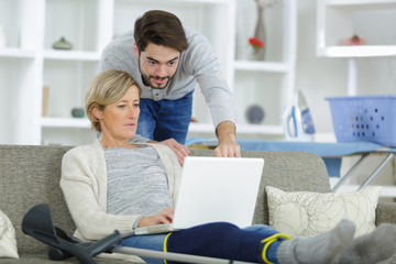 Man looking at laptop over shoulder of injured woman