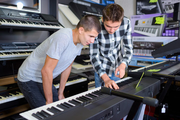Young men looking at keyboards in musical shop