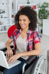 cheerful disabled woman using laptop on wheelchair at home