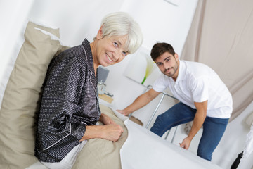 young man making senior womans bed