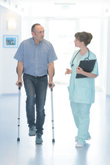 male patient with cast and surgeon walking on hospital corridor