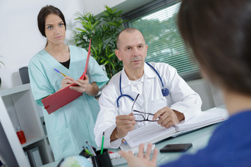 doctor and nurse talking to a patient in medical office